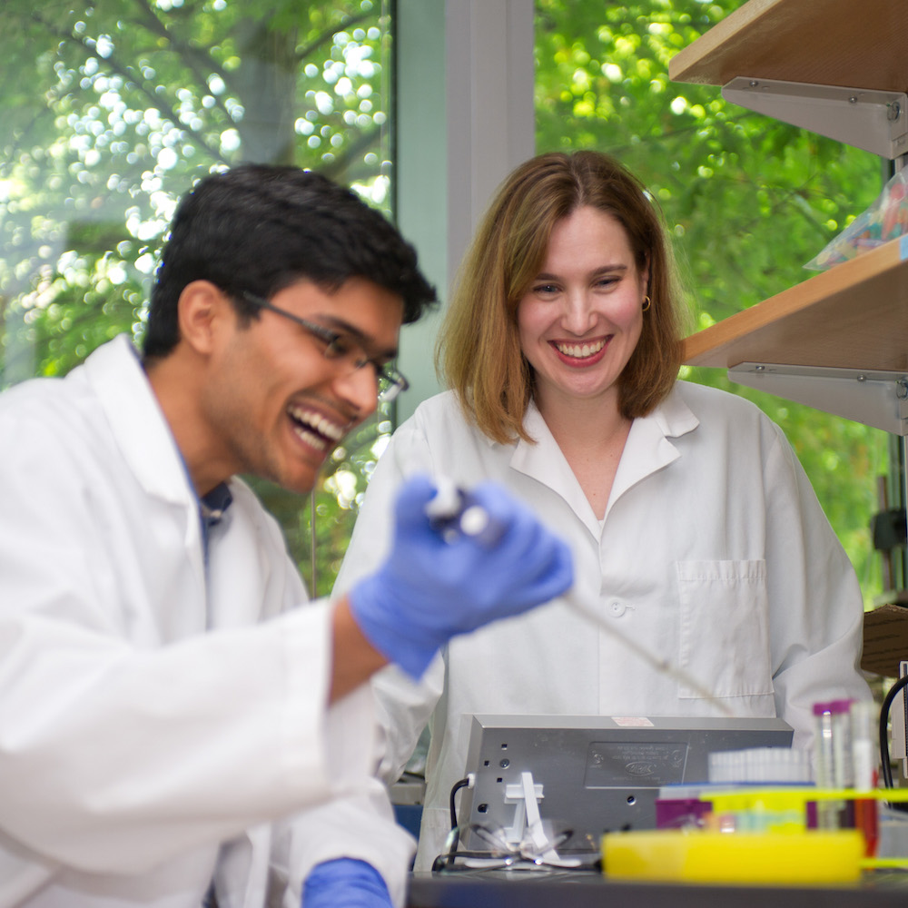 Two students laughing in a research lab.